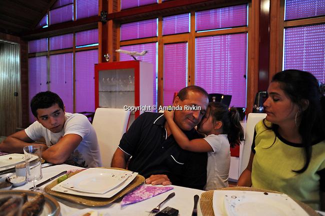Ibrahim Ibrahimov's granddaughter Cahan Guliyeva, 4, whispers in his ear as he sits at the dinner table with his son Huseyn Ibrahimov, 18, and daughter Ilkana Ibrahimova, 22, in his home between Sangachal and Sahil, Azerbaijan on August 16, 2012.