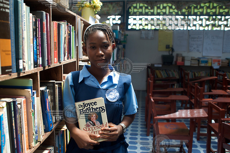 "Pam Massaquoi holding a book titled ""The Successful Woman"" by Dr. Joyce Brothers, in the school library."