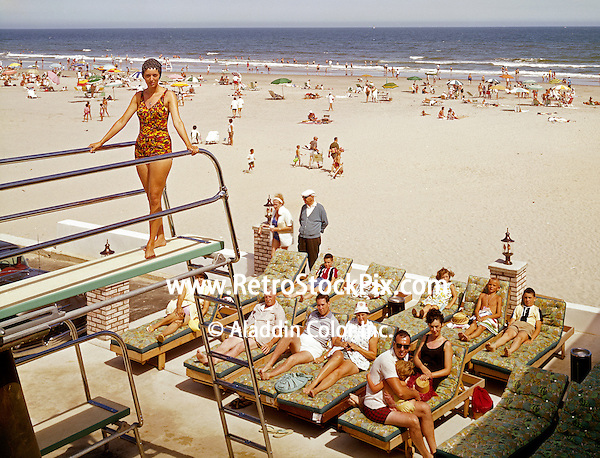 Young girl wearing a swim cap, standing on the high diving board of the Cavalier Motel. 1960's photograph