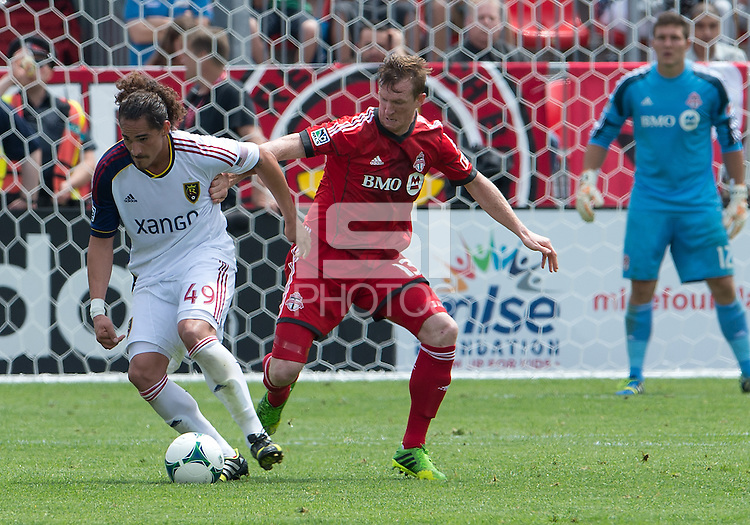 29 June 2013: Real Salt Lake forward Devon Sandoval #49 and Toronto FC defender Steven Caldwell #13 in action during an MLS game between Real Salt Lake and Toronto FC at BMO Field in Toronto, Ontario Canada.<br /> Real Salt Lake won 1-0.
