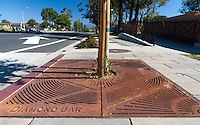 "Iron tree grates form the base of most of the trees planted for the Grand Avenue Beautification project.  This one has a lot of road and a ramp visible, including a large white arrow pointing away.  This was part of the 2015 rebuild of the Grand Avenue and Diamond Bar Boulevard intersection for Diamond Bar's 2015 ""Grand Avenue Beautification"" project, landscape architecture for the project was by David Volz Design."