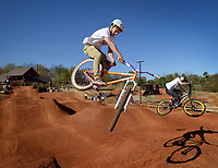 NWA Democrat-Gazette/BEN GOFF @NWABENGOFF<br /> Tanner Stolt (left) of Bentonville and Jared Calhoun of Sallisaw, Okla. catches air on the dirt jumps on Saturday Nov. 7, 2015 during opening day of The Railyard bike park in Rogers.