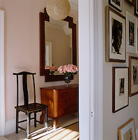 A Chinese wooden chair, 1940s style chest of drawers and a large mirror in the hall seen through the doorway to the living room