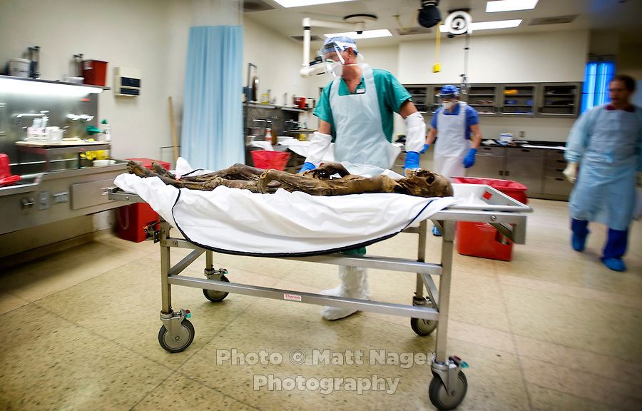 Assistant Louie Goad (cq) moves the corpse of a presumed migrant found on the Tohono O'odham reservation near Cockleburr Village on August 2,2009 in place for an autopsy examination at the Pima County Medical Examiners office in Tucson, Arizona, Wednesday, August 5, 2009. The person is thought to be a man and an identification card was found 30 feet from the body which might be his. ..PHOTOS/ MATT NAGER