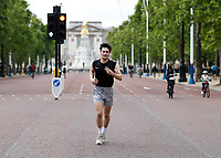 16th May 2020, London, England;  Runner wearing Crisis charity t shirt while running away from Buckingham Palace on the mall while not wearing gloves or a mask