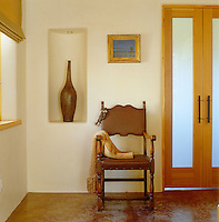 In the hallway of a contemporary New Mexico house the walls have been covered with raw plaster, tinted with native pigments and then polished with beeswax