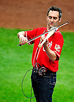 6 June 2010: Violinist Glenn Donnellan, a musician with the National Symphony Orchestra, plays his custom-made Louisville Slugger electric violin-bat at a game between the Washington Nationals and the Cincinnati Reds at Nationals Park in Washington, DC. The Reds edged out the Nationals 5-4 in a ten inning game. Mandatory Credit: Ed Wolfstein Photo