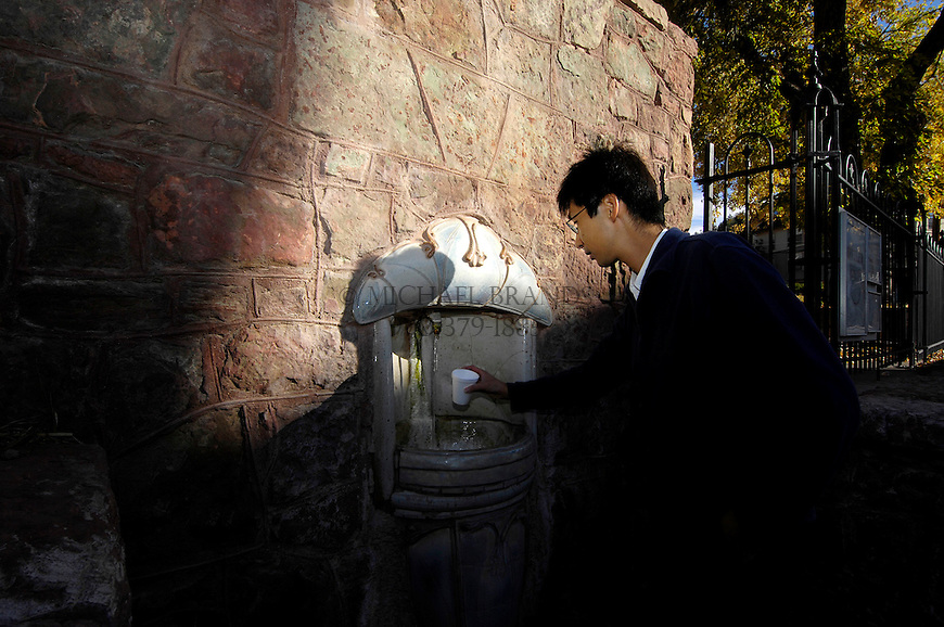 Tamuaki Toriya, from Japan, samples water at the Wheeler Spring. Michael Brands for The New York Times.