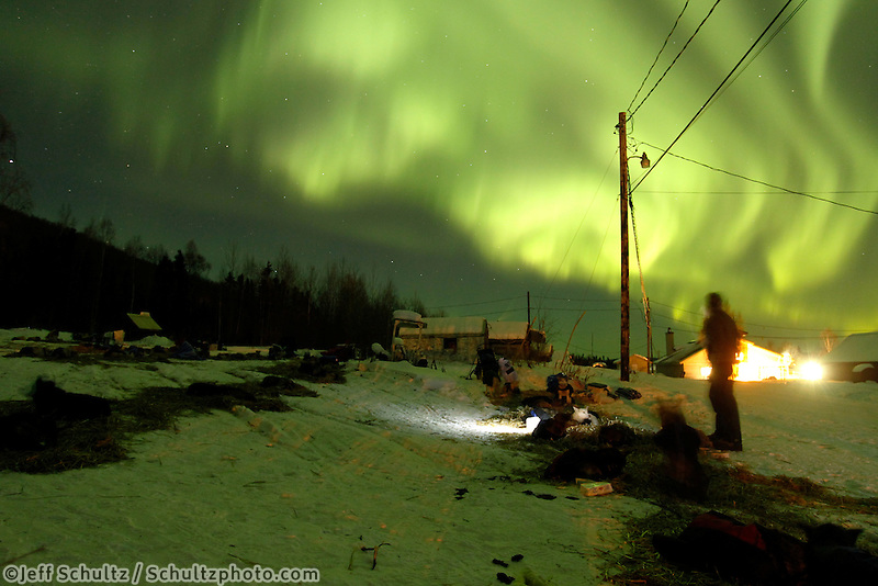 Musher Kristy Berington gazes up at the northern lights show at the Takotna checkpoint on Wednesday night during Iditarod 2011.