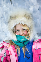 Julia Hicker, dressed in warm winter cloths poses for a portrait by frost covered branches, Wiseman, Alaska