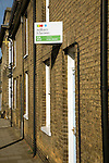 William Brown estate agent for sale sign on brick terraced house, Woodbridge, Suffolk, England