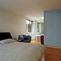 In the master bedroom a blue stucco wall separates the ensuite bathroom from the main sleeping area