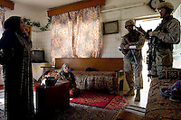 USMC Major Johnstone from the 6th CA group talks to women in their homes while  second platoon, Alfa company, 1st battalion, 506th, 101st airborne division is searching for insurgency weapons in other rooms during OPERATION TEEN WOLF, a raid in a neighborhood of western Ramadi with the purpose of searching for insurgency weapons, gather intel and meet with the civilian population, in the city of Ramadi, Iraq on Tuesday January 03 2006. during the raid four suspected Sunni insurgents were held  by the US military for further interrogations.