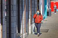 Pictured: A lone woman walks in the city centre wearing a face mask in Swansea, Wales, UK. Thursday 26 March 2020<br /> Re: Covid-19 Coronavirus pandemic, UK.