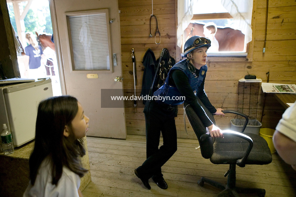 Jockey Julien Leparoux chats with stable staff and one of Patrick Biancone's daughters in the barn office at the Biancone stable in Saratoga Springs, NY, United States, after the early morning practice rides 5 August 2006.