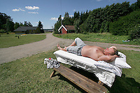 While some inmates enjoy a play, another enjoyes the sun outside the house where he lives...Bastøy Prison/Horten/Norway. ©Fredrik Naumann/Felix Features