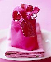 A small pink bag filled with wrapped presents and sweets on a place setting