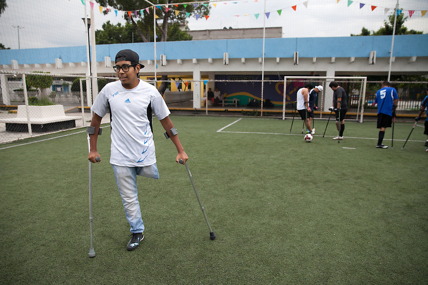 "Baruch, a player from Guerreros Aztecas, portrayed during a training session in Mexico City, Mexico on June 26, 2014. Baruch Alejandro Anleu Ramirez, 18, is the captain of Guerreros Aztecas. Two years ago, Baruch had his left leg amputated due to bone cancer. He used to practice as much as his chemotherapy would allow. Expelled from school for missing too many classes during his treatment, he says, ""Guerreros Aztecas has filled a big hole in my life"". Baruch was Guerreros Aztecas's brightest hope to represent Mexico at the Amputee Soccer World Cup. But since the cancer's spread to his lungs, he can no longer play or train with the team. Guerreros Aztecas (""Aztec Warriors"") is Mexico City's first amputee football team. Founded in July 2013 by five volunteers, they now have 23 players, seven of them have made the national team's shortlist to represent Mexico at this year's Amputee Soccer World Cup in Sinaloa this December. The team trains twice a week for weekend games with other teams. No prostheses are used, so field players missing a lower extremity can only play using crutches. Those missing an upper extremity play as goalkeepers. The teams play six per side with unlimited substitutions. Each half lasts 25 minutes. The causes of the amputations range from accidents to medical interventions – none of which have stopped the Guerreros Aztecas from continuing to play. The players' age, backgrounds and professions cover the full sweep of Mexican society, and they are united by the will to keep their heads held high in a country where discrimination against the disabled remains widespread. (Photo by Bénédicte Desrus)"