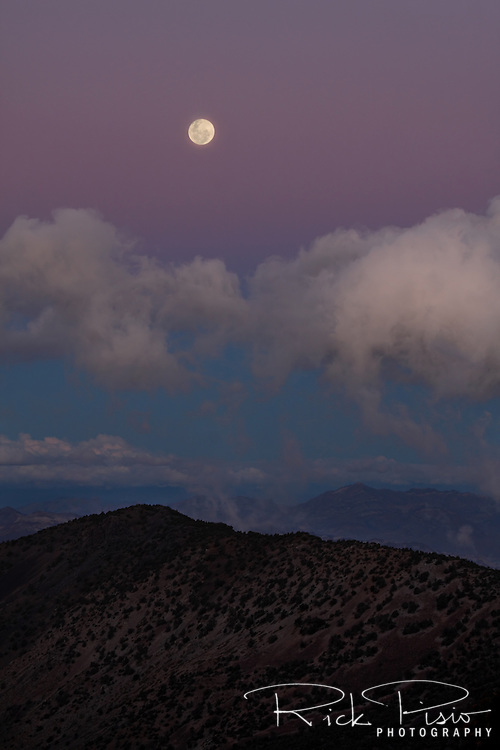 A full moon rises above Death Valley National Park as seen from Mohogany Flat.