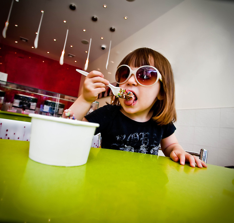 Little girl wearing sunglasses eating ice cream