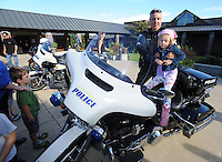 NWA Democrat-Gazette/ANDY SHUPE<br /> Cpl. Robert Hargus with the Fayetteville Police Department lifts Elyse Williams, 4, Wednesday, Sept. 23, 2015, during the first day of the annual First School Trike Rally at First United Presbyterian Church in Fayetteville. The event, which serves as a fundraiser for St. Jude's Children's Hospital, features bike riding, temporary tattoos, snow cones, a bike wash and demonstrations from the Fayetteville Police Department. Visit nwadg.com/photos to see more photographs from the morning.