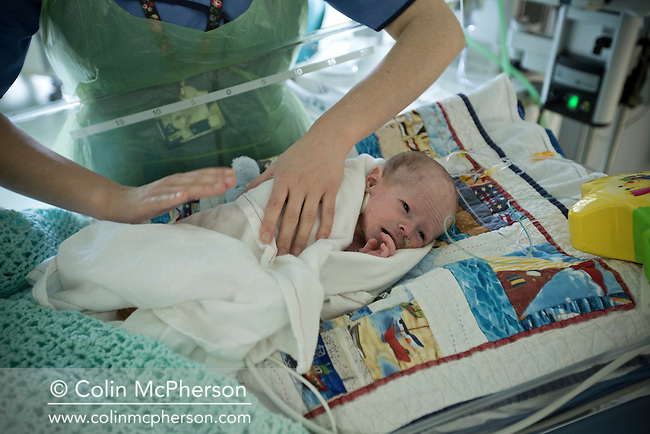 A female nurse watching attending to three-and-a-half-week-old Finn Jones at the paediatric intensive care unit at Evelina London Children's Hospital in central London. The son of Philip and Kathryn Jones from Canterbury, Kent, Finn was born with a pre-diagnosed condition which required a life-saving, five-hour heart 'switch' operation to be carried out within the first two weeks of his life. The operation, which took place when Finn was 10 days old was successful, however, due to other near fatal complications the his recovery during the subsequent six weeks was slow and difficult.