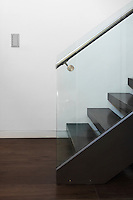 A modern dark wood staircase with glass side panel and steel banister.