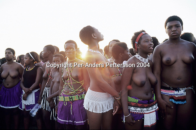 NONGOMA, SOUTH AFRICA - SEPTEMBER 11: Unidentified maidens wait to perform at the Royal Palace as the suns sets during the annual Reed Dance on September 11, 2004 in Nongoma in rural Natal, South Africa. About 20.000 maidens from all over South Africa arrived to dance for Zulu King Goodwill Zwelethini at the Enyokeni Royal Palace in Kwa-Nongoma about 350 kilometers from Durban. The girls come to the kingdom to declare their virginity and the ceremony encourages girls and young women to abstain from sexual activity to curb the spread of HIV-Aids.(Photo: Per-Anders Pettersson)......