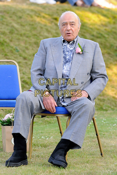 "MOHAMED AL FAYED.At ""Lawnfest"", an open air concert, West Heath School, Sevenoaks, Kent, England..June 25th, 2009.full length mohammed grey gray suit blue pattern shirt pink flower corsage black boots sitting .CAP/FIN.©Steve Finn/Capital Pictures."