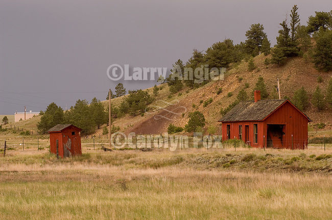 Red wooden outhouse behind abandoned narrow gauge railroad station, gathering storm, Colorado Rockys