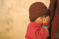 A young girl from the minority Tajik ethnic group in Xinjiang, China  peeks out from the safety of her mothers embrace. The nearly 30,000 semi-nomadic Muslim Tajiks live in Xinjiang, 60% living in Tashkurgan Tajik Autonomous County..