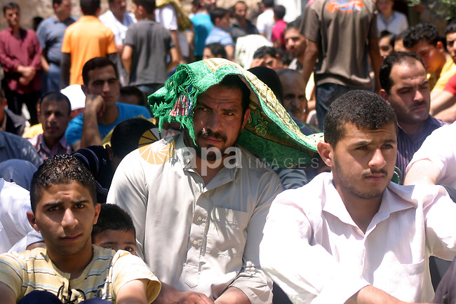 Palestinians attend the third friday prayer of Islam's holy fasting month of Ramadan outside the Ibrahimi mosque, or the Tomb of the Patriarchs, in the divided West Bank city of Hebron on August 19, 2011. Photo by Najeh Hashlamoun