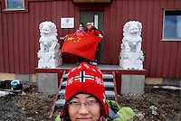 photograph by XAVIER CERVERA 06/2010.cantonese woman Luo Jun and her husband pose with the national flag in the only chinese scientific station ('Yellow river' is called) in the Arctic, in the Science Village of Svalbard: Ny-Alesund (at 79º parallel north), in west Spitsbergen island. Two lions guard the entrance according to feng shui tradition