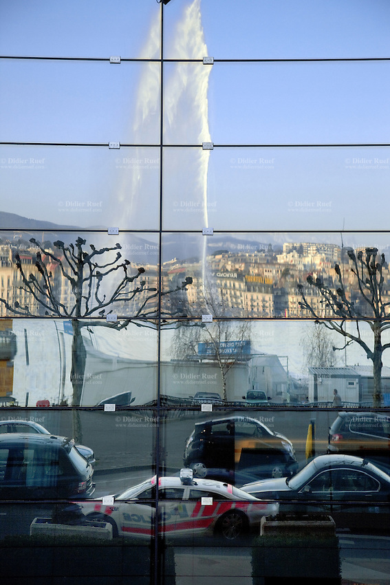 Switzerland. Geneva. Paquis neighborhood. A view on the Geneva Water Fountain and a police car, bot are reflected on the glass facade of the Grand Hotel Kempinsky Geneva, a Luxury 5 star hotel located right on Lake Geneva. The elegant Geneva Water Fountain (Jet d'Eau de Genève) is the lakeshore's star attraction dazzling visitors as it shoots 140 metres into the sky. 15.03.12 © 2012 Didier Ruef..