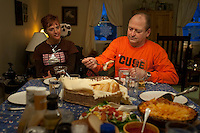 Kara's father helps her with her meal during a family dinner on Valentine's Day. Photo by James R. Evans ©