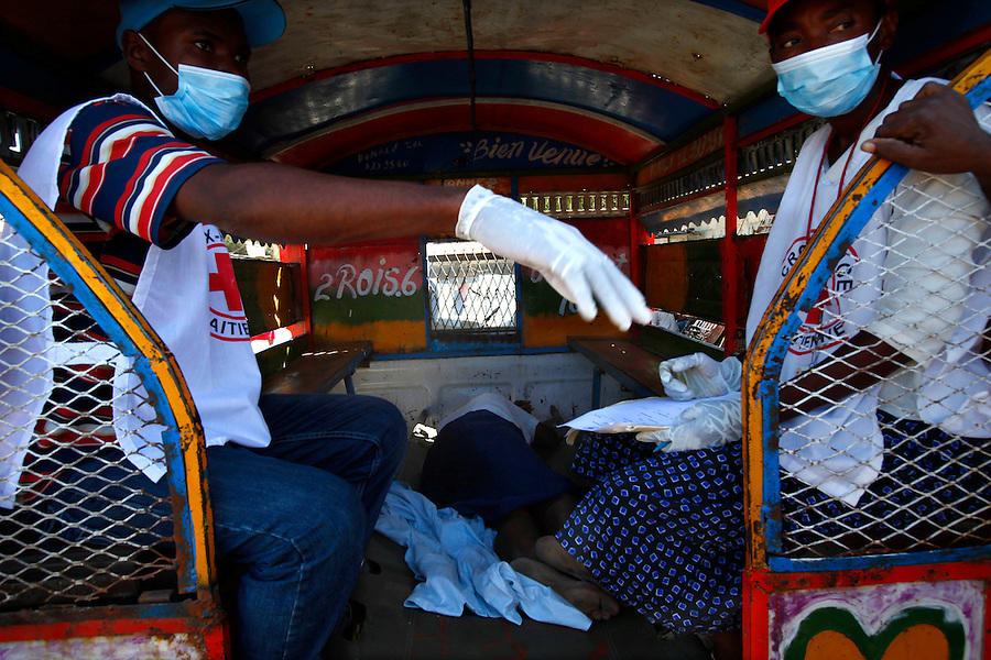 Nov 10, 2010 - Port-au-Prince, Haiti.A local residents suffering from cholera-like symptoms lies in the back of a tap-tap bus as officials discuss where to take her after she was taken from a small medical clinic set up in tents in the Cite Soleil area of Port-au-Prince, Haiti, Wednesday, November 10, 2010 as fears of a cholera outbreak spread through the area just two days after cases of the infection were confirmed in the area, the poorest slum in Haiti's capital. Officials from the Pan American Health Organization warn that Haiti's cholera epidemic, spread primarily through consuming infected water and food, is likely to grow much larger in the wake of Hurricane Tomas.  (Credit Image: Brian Blanco/ZUMA Press) 1