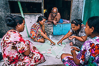 Residents play cards for small stakes outside a shack in the Northern Camp slum.