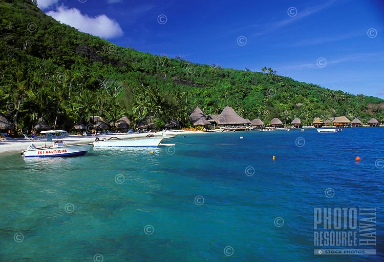 Water front beach bungalows and boats in Bora Bora, Tahiti
