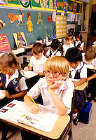 Students in private school class grade 4 and 5 at desks and learning in schoo