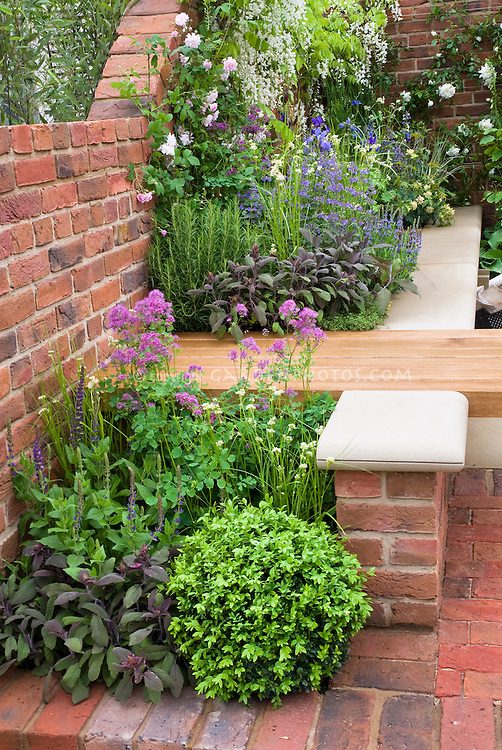 Sitting next to fragrant herbs and flowers garden bench for Brick flower garden designs