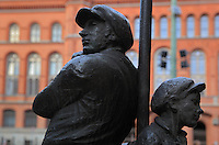Statue of workers wearing flat caps in Am Nussbaum Strasse, with the Rotes Rathaus (Red City Hall) in the background, Mitte, Berlin, Germany. Picture by Manuel Cohen