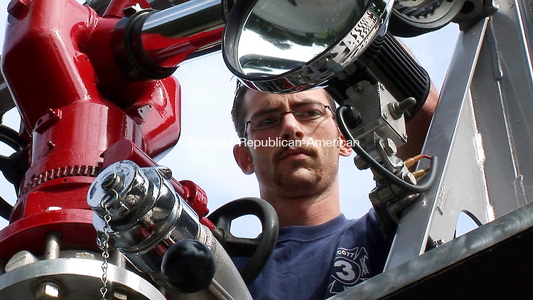 WOLCOTT, CT. 06 September 2006--090606SV01--Firefighter Mike Couture Jr. checks the operation of a master stream on the ladder truck at Wolcott Volunteer Fire Department Company 3 during a drill at the company Wednesday morning. The weekly maintained checks keep the apparatus ready for service.<br /> Steven Valenti Republican-American