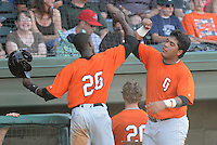 Center fielder Evan Crawford (26) of the Augusta GreenJackets, left, is congratulated after scoring a run by teammate Hector Sanchez (37) in a game against the Greenville Drive on May 23, 2010, at Fluor Field at the West End in Greenville, S.C. Photo by: Tom Priddy/Four Seam Images