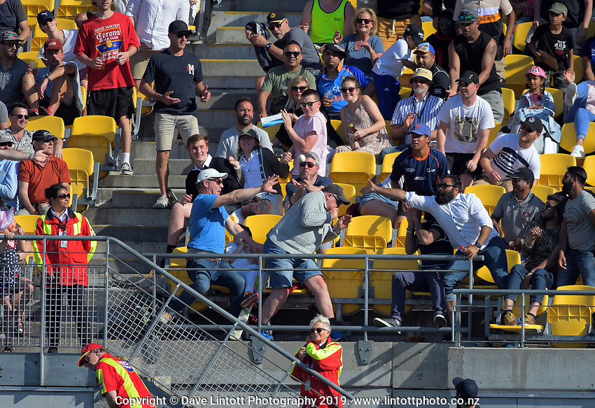 Fans try to catch a six (or avoid it). Twenty20 International cricket match between NZ Black Caps and England at Westpac Stadium in Wellington, New Zealand on Sunday, 3 November 2019. Photo: Dave Lintott / lintottphoto.co.nz
