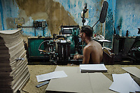 A Cuban master printer operating a printing machine in the state print shop, Santiago de Cuba, Cuba, 4 August 2008.