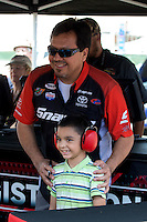 Jul. 26, 2013; Sonoma, CA, USA: A young fan poses with NHRA funny car driver Cruz Pedregon during qualifying for the Sonoma Nationals at Sonoma Raceway. Mandatory Credit: Mark J. Rebilas-