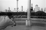 The Peoples Republic of China. Shanghai. 2000.  On the Bund a young Chinese tourist poses for her photograph. .
