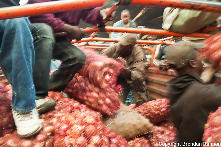 Porters  unloading a truck full of red onions at Wakuli market in Nairobi, Kenya.