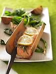 Salmon wrapped in cedar wood and baked, with grilled apples and asparagus, topped with lemon slices and rosemary.