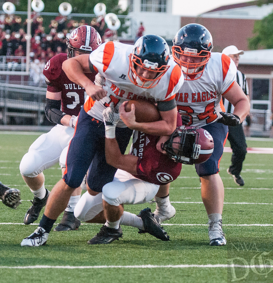 NWA Democrat-Gazette/ANTHONY REYES &bull; @NWATONYR<br /> Dylan Qualls (15) of Rogers Heritage plows through Chris Crawford (22) of Springdale Friday, Sept. 23, 2016 for a touchdown at Jarrell Williams Bulldog Stadium in Springdale.